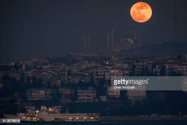 A ferry passes in front of the Super Blue Blood Moon rising behind the Camlica Mosque on January 31 2018 in Istanbul Turkey A Super Blue Blood Moon...