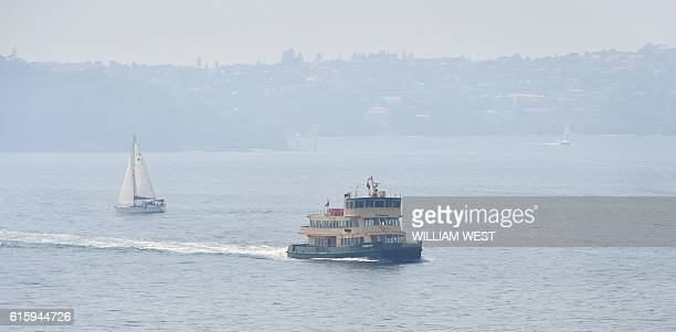 A ferry plies its trade in Sydney Harbour with the city shrouded in smoke on October 21 2016 The smoke drifted over the city from burnoffs on the...