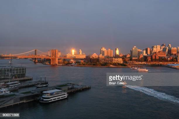 A ferry rides on the East River towards the Brooklyn Bridge in New York City