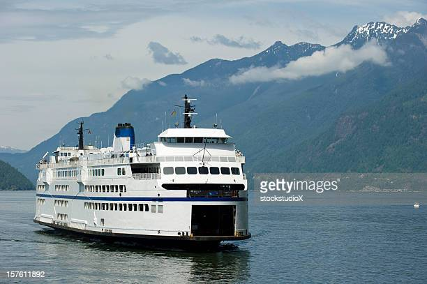 a ferry sailing through a waterway surrounded by hills - british columbia stock pictures, royalty-free photos & images