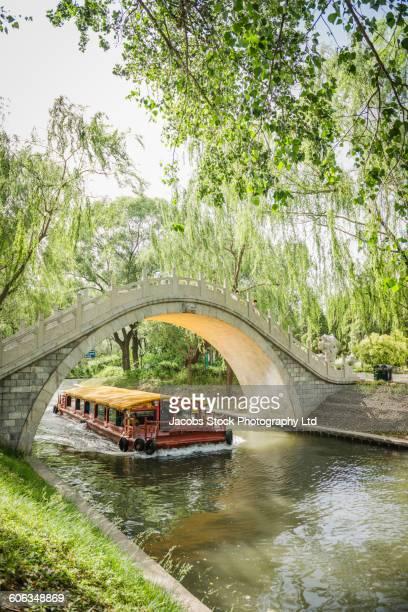 Ferry sailing under bridge in park