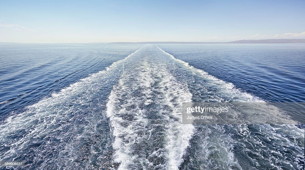 ferry trails in calm ocean. : Stock Photo