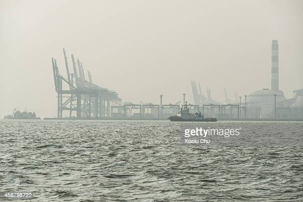 A ferry travels across a smogcovered Xiamen Port on November 11 2014 in Xiamen China Xiamen is located on the southeast coast of Mainland China is a...