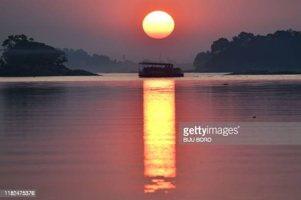 Ferry travels along the river Brahmaputra during sunset in Guwahati on November 15, 2019.