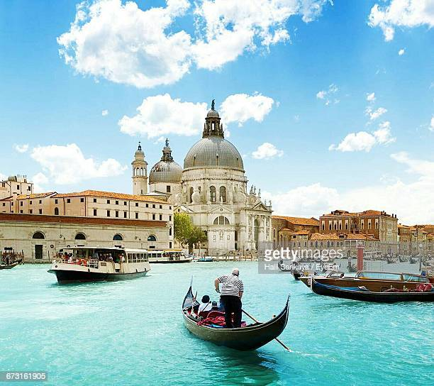 ferry with gondolas sailing in grand canal by santa maria della salute against sky - venezia foto e immagini stock