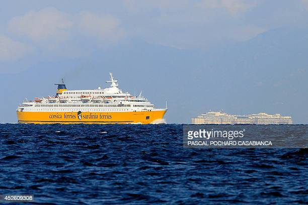 A ferryboat from company Corsica Ferries navigates on the sea during the towing of the Costa Concordia cruise ship wreck on July 24 2014 near Bastia...
