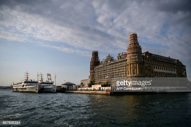 TOPSHOT Ferryboats are docked in front of the historical haydarpasa train station as scaffolding are seen on the building on August 23 2017 during a...