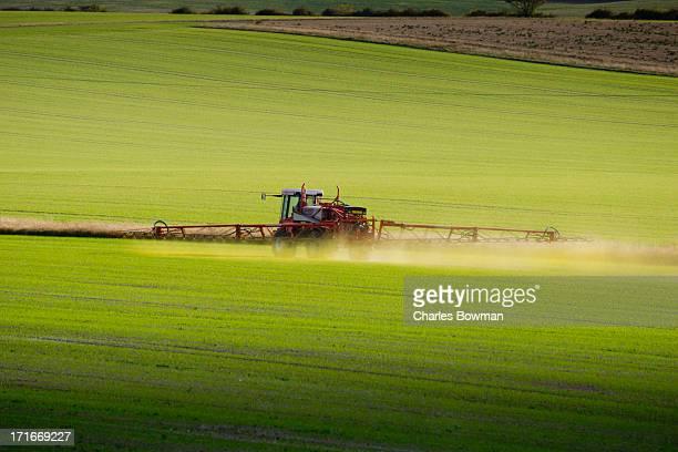 Fertiliser spraying tractor rides across field
