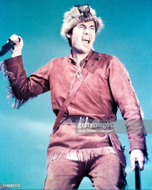 Fess Parker US actor holding a knife and wearing a coonskin hat in a publicity portrait for the television series 'Davy Crockett King of the Wild...
