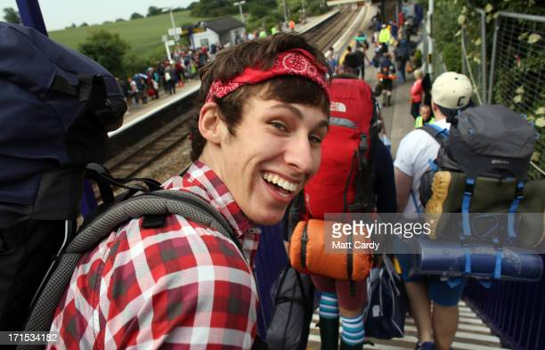 Festival attendees arrive at Castle Cary railway station to travel onwards to the Glastonbury Festival site at Worthy Farm Pilton on June 26 2013...