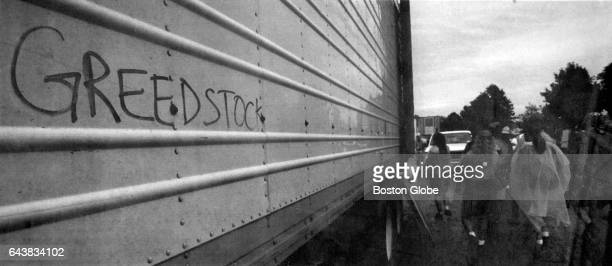 """Festival attendees leave Woodstock '94, passing by graffiti on a concession stand truck reading """"Greedstock"""" in Saugerties, NY on Aug. 14, 1994."""