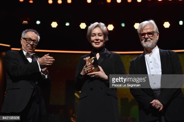 Festival director Dieter Kosslick applauds costume designer Milena Canonero on stage as she receives her honorary Golden Bear next to producer Jan...