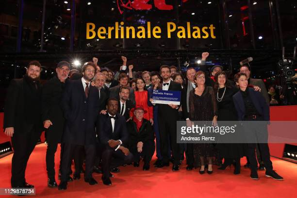 Festival director Dieter Kosslick poses with cast and crew members at the Marighella premiere during the 69th Berlinale International Film Festival...