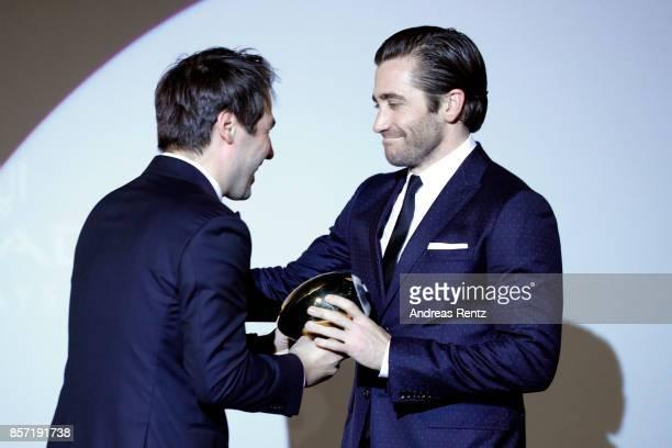 Festival director Karl Spoerri hands over the Golden Eye Award to Jake Gyllenhaal at the 'Stronger' premiere at the 13th Zurich Film Festival on...