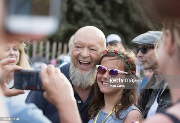 Festival founder Michael Eavis is greeted by festival goers at the Avalon Cafe at the Glastonbury Festival site at Worthy Farm in Pilton on June 22...