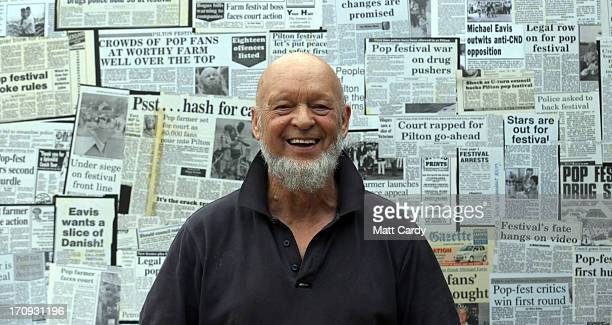 Festival founder Michael Eavis poses for a photograph in front of old press clippings displayed at Goose Hall the onsite staff canteen at the...