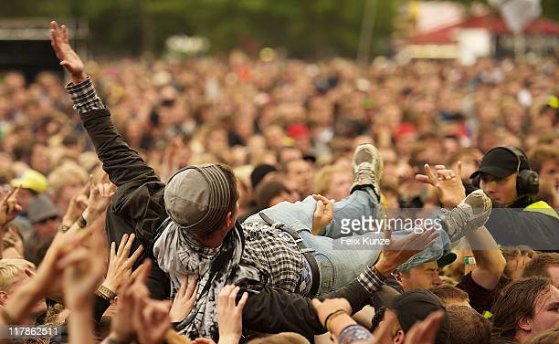 A festival goer crowd surfs in a general view of crowd atmosphere on day two of the Roskilde Festival on July 1 2011 in Roskilde Denmark