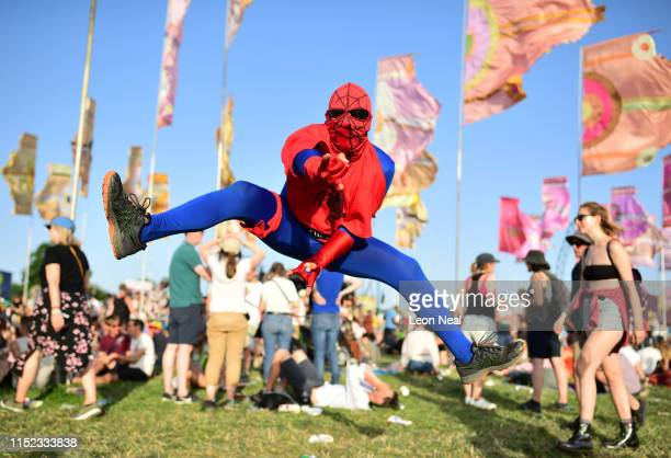 A festival goer dressed as Spiderman jumps in the air during day two of Glastonbury Festival at Worthy Farm Pilton on June 27 2019 in Glastonbury...