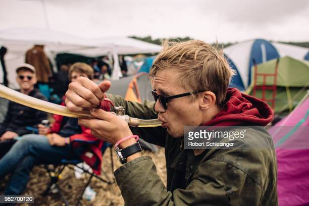 Festival goer drinks beer through a hose during the third day of the Hurricane festival on June 24, 2018 in Scheessel, Germany.