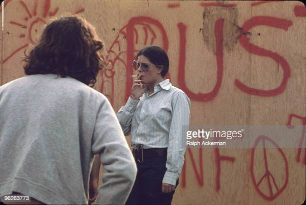 A festival goer in a buttondown shirt and large octagonalframed glaases smokes a cigarette near a graffiticovered plywood wall on the grounds of the...