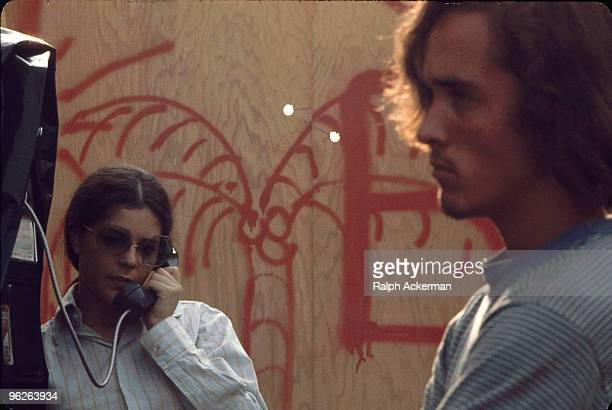 A festival goer in a buttondown shirt and large octagonalframed glaases talks on a pay telephone near a graffiticovered plywood wall on the grounds...