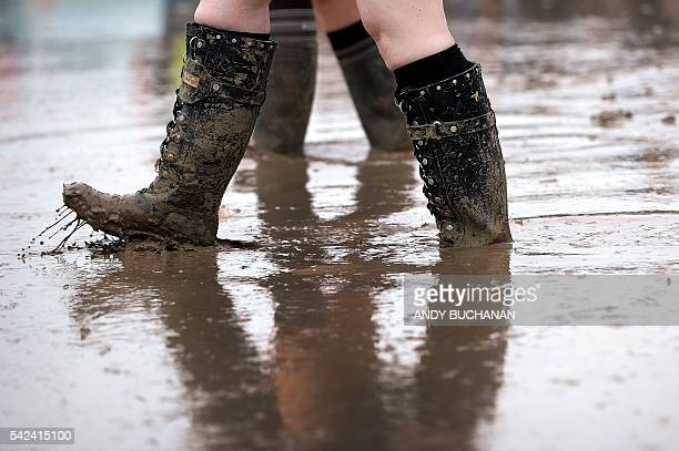 Festival goer in wellies walks through a muddy puddle as she makes her way through the site at Glastonbury Festival of Music and Performing Arts on...