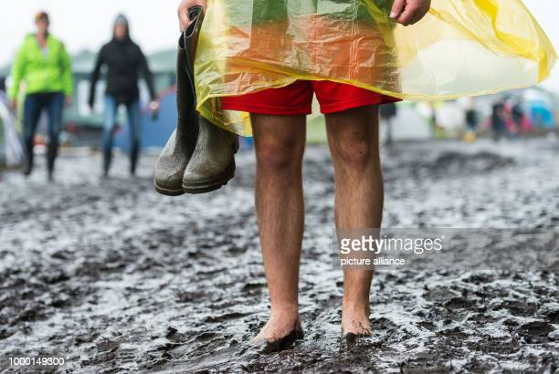 Festival goer presents his boots while standing in watery mud at the Hurricane Festival in Scheeßel, Germany, 24 June 2017. The 21st edition of the...