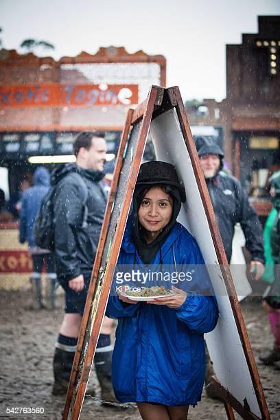 Festival goer shelters from the rain on Day 1 of the Glastonbury Festival 2016 at Worthy Farm Pilton on June 24 2016 in Glastonbury England
