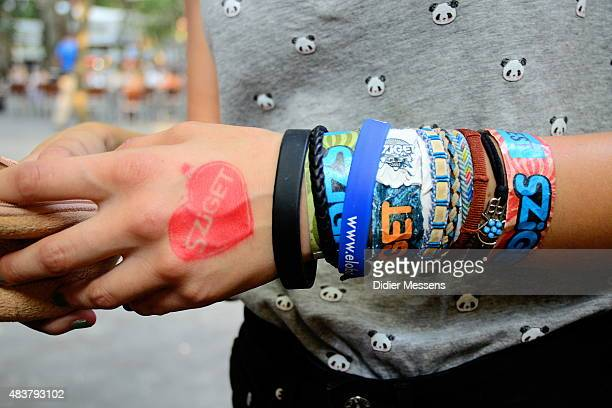 A festival goer show his collection of bracelet from Sziget festival at Obudai Island on August 12 2015 in Budapest Hungary