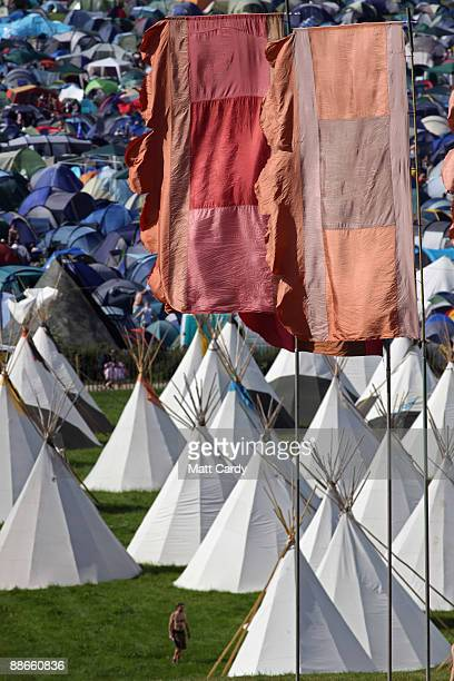Festival goer walks passed in front of the tipi field as music fans start to arrive at the Glastonbury Festival site at Worthy Farm, Pilton on June...