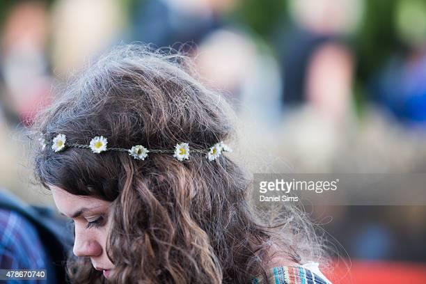 A festival goer wears a flower head band at the Glastonbury Festival at Worthy Farm Pilton on June 26 2015 in Glastonbury England