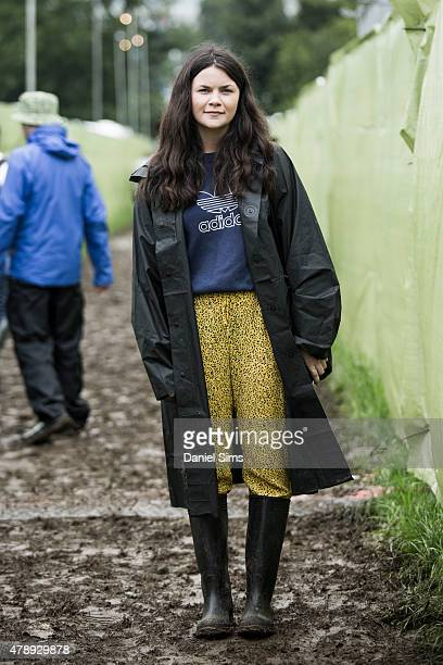 Festival goer wears a Muji coat Adidas top Zara trousers and a Primark bag at the Glastonbury Festival at Worthy Farm Pilton on June 28 2015 in...