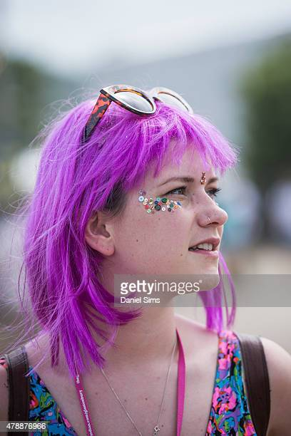 A festival goer with dyed purple hair at the Glastonbury Festival at Worthy Farm Pilton on June 27 2015 in Glastonbury England