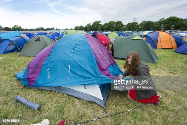 Festival goers Alyssa Browne and Christine Thurlow set their tent up at the Glastonbury Festival at Worthy Farm in Somerset
