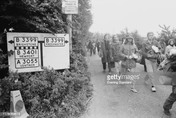 Festival goers and music fans walk along a road towards the village of Freshwater to attend the Isle of Wight Festival 1970, in August 1970.