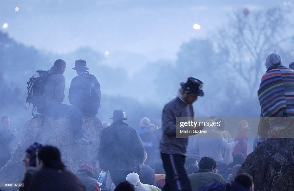 Festival goers at Glastonbury Stone Circle in a blue mist at dawn waiting for the sun to come up, 28th June 2004.