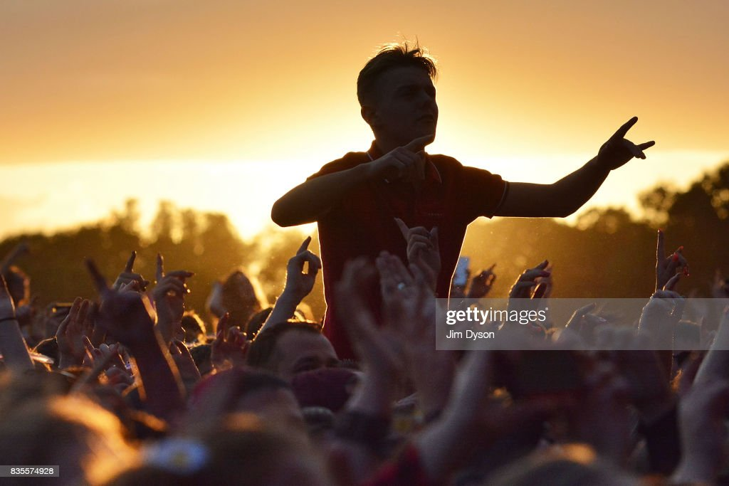 Festival goers at sunset during V Festival 2017 at Hylands Park on August 19, 2017 in Chelmsford, England.