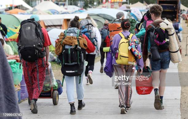Festival goers carry tents and bags on their journey home at the 2019 Glastonbury Festival held at Worthy Farm, in Pilton, Somerset on July 1, 2019...
