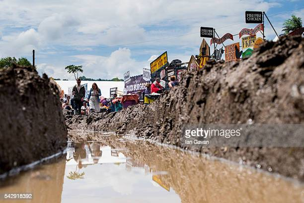 Festival goers cope with muddy conditions on day 2 of the Glastonbury Festival at Worthy Farm Pilton on June 25 2016 in Glastonbury England Now in...