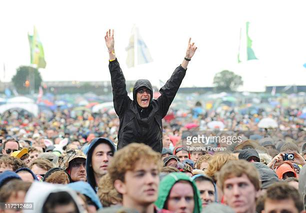 Festival goers don't let the rain spoil the atmosphere of the crowd as they watch The Vaccines perform on the Other stage during the second day of...