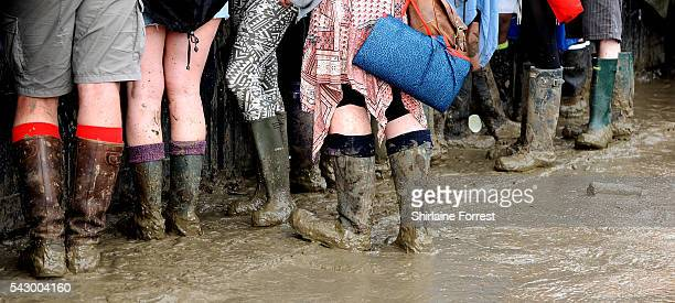 Festival goers endure the mud while enjoying Glastonbury Festival 2016 at Worthy Farm Pilton on June 25 2016 in Glastonbury England