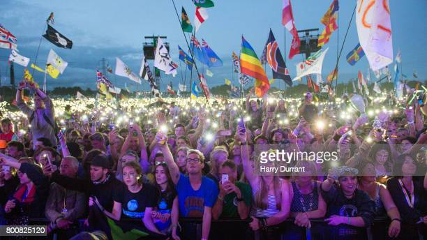 Festival goers enjoy the atmosphere as Ed Sheeran performs on The Pyramid Stage on day 4 of the Glastonbury Festival 2017 at Worthy Farm Pilton on...