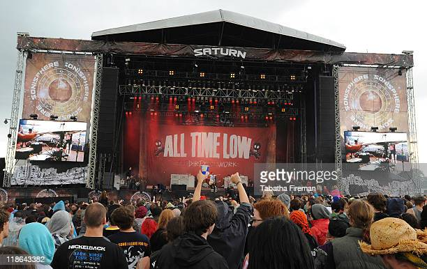Festival goers enjoy the atmosphere of the crowd as they watch All Time Low perform on the Saturn stage during the second day of Sonisphere 2011 at...