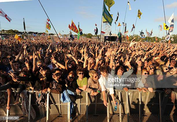 Festival goers enjoy the atmosphere of the crowd whilst watching Elbow perform on the Pyramid stage during the third day of Glastonbury Festival at...