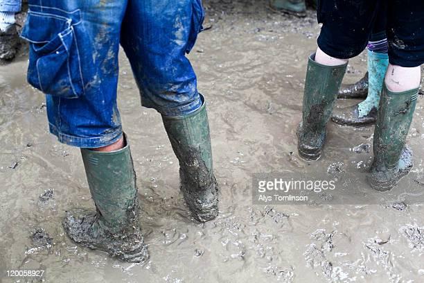 festival goers in mud at glastonbury festival 2011 - festivalero fotografías e imágenes de stock