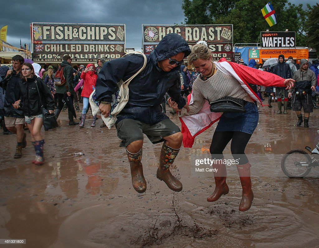 Festival goers jump in mud at Worthy Farm in Pilton during the 2014 Glastonbury Festival on June 27, 2014 in Glastonbury, England. Gates opened on Wednesday at the Somerset dairy farm that plays host to one of the largest music festivals in the world. Tickets to the event, which is now in its 44th year, sold out in minutes even before any of the headline acts had been confirmed. The festival, which started in 1970 when several hundred hippies paid £1, now attracts more than 175,000 people.