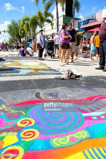 Festival goers look at chalk street art drawings