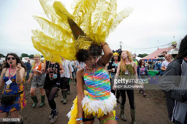TOPSHOT Festival goers make their way through the site at the Glastonbury Festival of Music and Performing Arts on Worthy Farm near the village of...