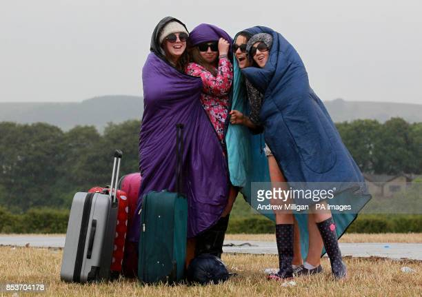 Festival goers Megan Williamson, Emma McIntosh, Chloe Thomson and Lynne Cheriffs shelter from the rain at the T in the Park music festival at Balado...
