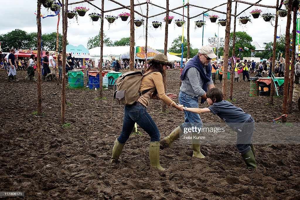 Festival goers negotiate the mud during the third day of Glastonbury Festival 2011 at Worthy Farm on June 25, 2011 in Glastonbury, United Kingdom.